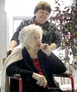 Juanita Taylor, a 101-year-old resident at The Leopold Retirement Residence, waits for an elevator with her Circle of Life caregiver, Jan Fransen, Thursday, Feb. 13, 2014, at the Leopold Retirement Residence in Bellingham. Circle of Life is worker-owned care giving cooperative aimed to assist elderly and disabled people in Whatcom County. DANNY MILLER — THE BELLINGHAM HERALD